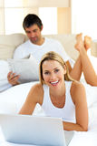 Pretty woman using a laptop lying on bed Stock Image