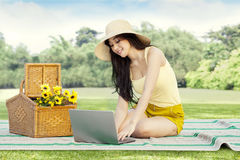 Pretty woman using laptop on mat at field Stock Images