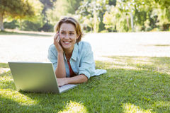 Pretty woman using laptop in park Royalty Free Stock Image
