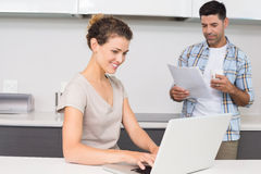 Pretty woman using laptop while partner reads the newspaper Stock Photography