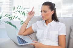 Pretty woman using laptop sitting on cosy sofa Royalty Free Stock Photos