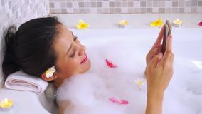 Pretty woman using mobile phone on bathtub. Video footage of a young pretty woman relaxing on bathtub while using a mobile phone stock video footage