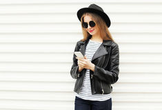 Pretty woman using smartphone in rock black style over white Stock Photos