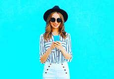 Pretty woman is using a smartphone wearing a black hat and handbag. Clutch over colorful blue background in the city Royalty Free Stock Images