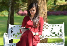 Pretty  woman using  tablet. In the garden Royalty Free Stock Photography