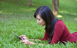 Pretty woman using tablet. Outdoor laying on grass Royalty Free Stock Images