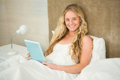 Pretty woman using tablet computer in her bed Royalty Free Stock Photography