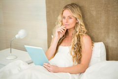 Pretty woman using tablet computer in her bed Royalty Free Stock Image