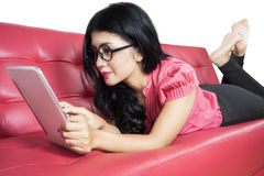 Pretty woman using tablet on couch Royalty Free Stock Image