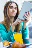 Pretty woman using tablet while having breakfast in coffee shop Royalty Free Stock Photo
