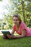 Pretty woman using tablet in park. On a sunny day Royalty Free Stock Images