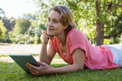 Pretty woman using tablet in park. On a sunny day Stock Images