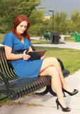 Pretty Woman using Tablet sitting on Park Bench Stock Images