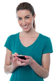 Pretty woman using touch screen cellphone Royalty Free Stock Photography