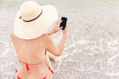 Pretty woman on vacation is sitting on the beach with mobile. Royalty Free Stock Image