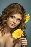 Pretty woman. The very pretty red-haired blue eyed young woman with yellow flower, smile , vertical close up portrait stock photography