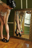 Pretty woman in vintage gown looking in the mirror. To her long legs Stock Photos