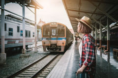 Pretty woman waiting the train at train station for travel in su. Mmer. Travel concept royalty free stock photo