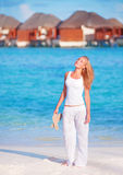 Pretty woman walking along beach Royalty Free Stock Photography