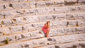 Pretty woman walking in Antique Theater. In ancient city Myra, Turkey. Sits on the stone in the centre stock video footage
