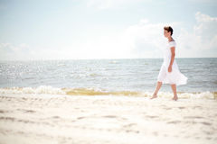 Pretty Woman Walking the Beach Stock Images