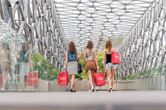 3 Pretty woman walking on the bridge, they go shopping - back photo Stock Photos