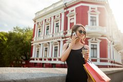 Pretty woman walking down the street. Young attractive feminine girl smiling, walking near red building, looking aside Royalty Free Stock Images