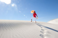 Pretty woman walking up sand dune in summer heat Royalty Free Stock Photos