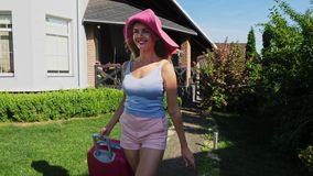 Pretty woman walks with suitcase outside in a sunny day. A woman wearing a pink hat stock video footage