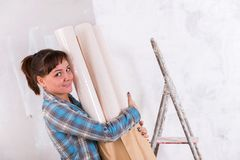 Pretty woman with wallpapers going repair house stock photo