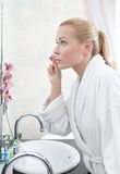 Pretty woman washes face with lotion Royalty Free Stock Photography