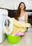 Pretty woman washing clothes in washer Stock Image