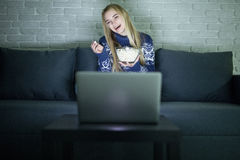 Pretty woman watching movie on her laptop in bed in a dark room watching movie late night. Royalty Free Stock Image