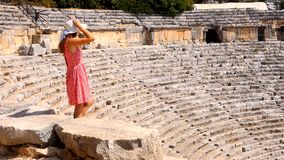 Pretty woman watching the ruins of antique theater. In ancient city Myra, Turkey stock video footage