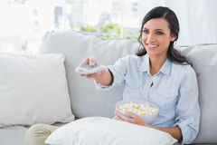 Pretty woman watching tv eating popcorn Stock Images