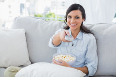 Pretty woman watching tv with popcorn. In her living room Stock Photos