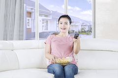 Pretty woman watching tv on sofa. Photo of a pretty woman watching television on the sofa while eating popcorn and holding a remote control Royalty Free Stock Photography