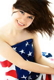 Pretty woman wearing an American flag. Happy beautiful young brunette woman wrapped into an American flag Royalty Free Stock Photography