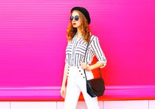 Pretty woman wearing a black hat sunglasses white pants. And handbag clutch over colorful pink background royalty free stock photos