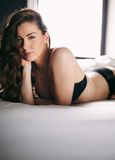 Pretty woman wearing black lingerie lying on bed Stock Photo