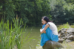 Pretty woman wearing blue skirt posing in nature and sitting on Stock Image