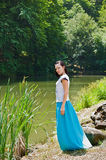 Pretty woman wearing blue skirt posing in nature Stock Photography