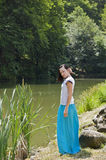 Pretty woman wearing blue skirt posing in nature Stock Photos