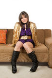 Pretty woman wearing boots sitting on a sofa Royalty Free Stock Image