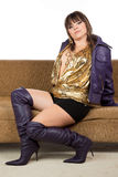 Pretty woman wearing boots sitting on a sofa Stock Image