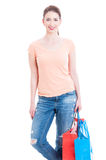 Pretty woman wearing casual jeans and holding paper shopping bag Stock Photos