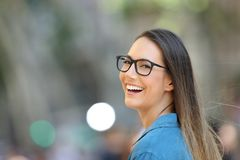 Pretty woman wearing eyeglasses looking at camera. Pretty woman wearing eyeglasses smiling looking at camera in the street royalty free stock photos