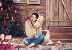 Pretty woman wearing fur coat sitting near the Christmas tree Stock Image