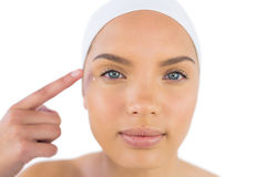 Pretty woman wearing headband putting cream on her face Stock Image
