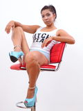 Pretty woman wearing high heels sits on red stool Royalty Free Stock Photography